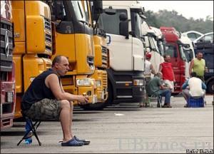 Фуры стоят в ряд на стоянке, водители отдыхают.