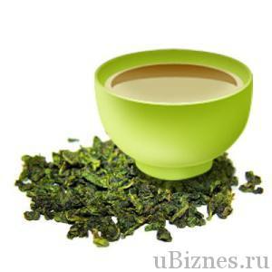 Зеленая чашка с чаем Тай Ши У-лун и рассыпанный чай на белом фоне