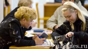 Девушка роется в сумке, в то время кк женщина разглядывает ее документы