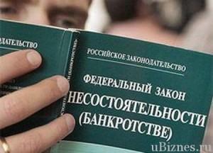 Мужчина смотрит в книгу с законом о банкротстве