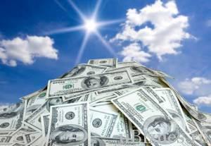 Кучка долларов на фоне ясного неба
