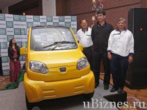 Маленькая желтая машина - Bajaj RE60 стоит на подиуме, рядом три человека
